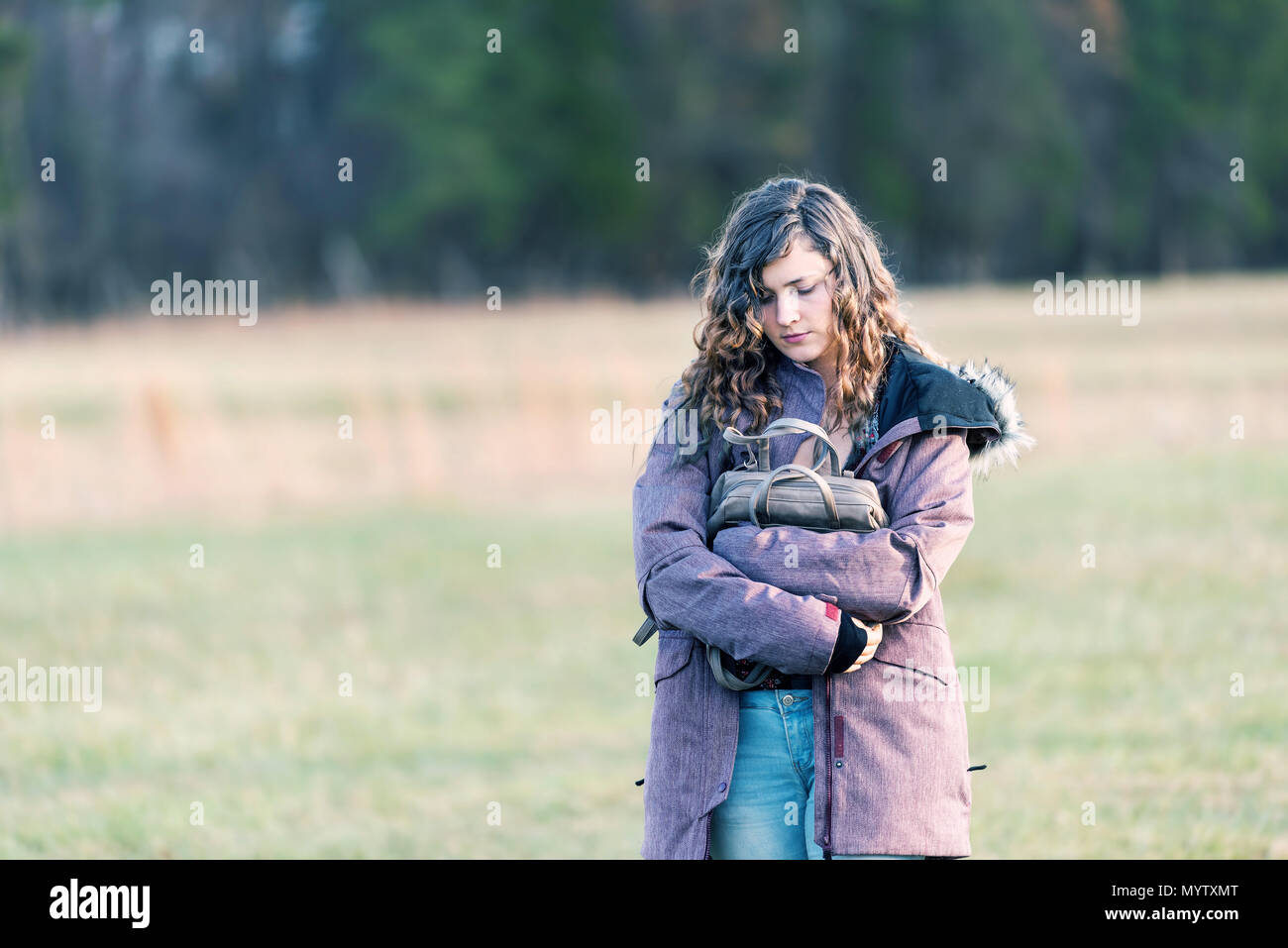 Young sad woman girl walking with head eyes closed down holding hugging purse in winter coat, unhappy stomach ache pain - Stock Image