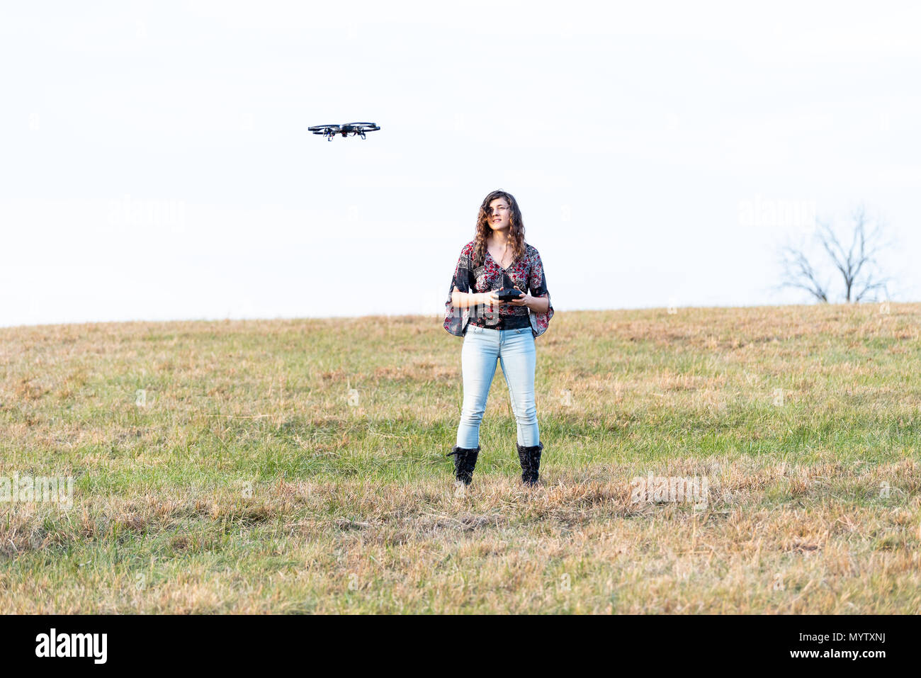 Young happy smiling woman controlling video camera drone in autumn or fall with boots in park in Virginia countryside open field hill - Stock Image