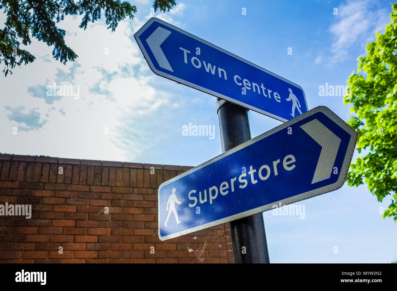 Town Centre vs Superstore - Signs pointing shoppers to the Town Centre shopping or a nearby Superstore - Out of Town Shopping vs Town Centre - Stock Image