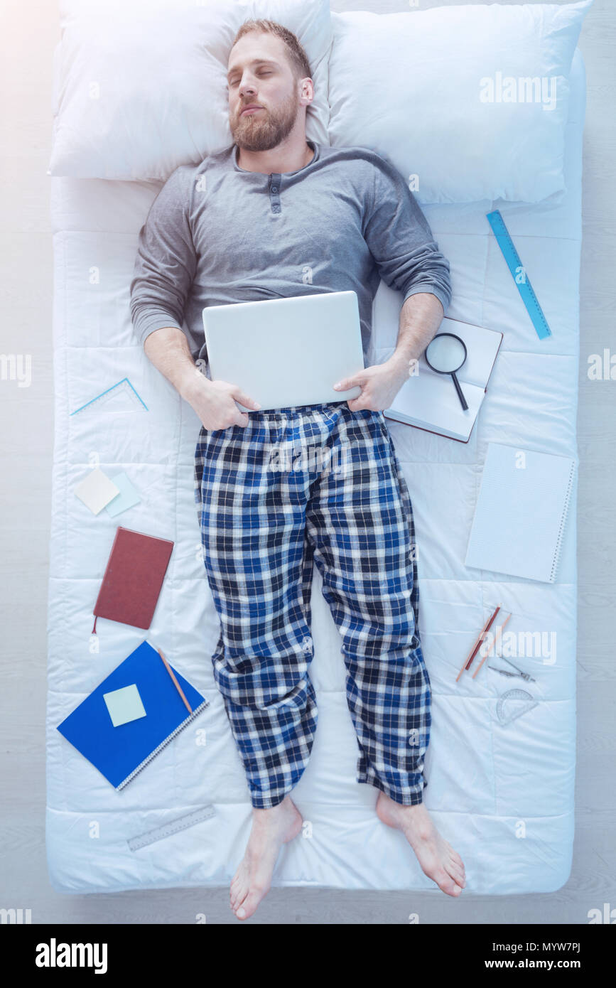 Educated young guy falling asleep while studying - Stock Image