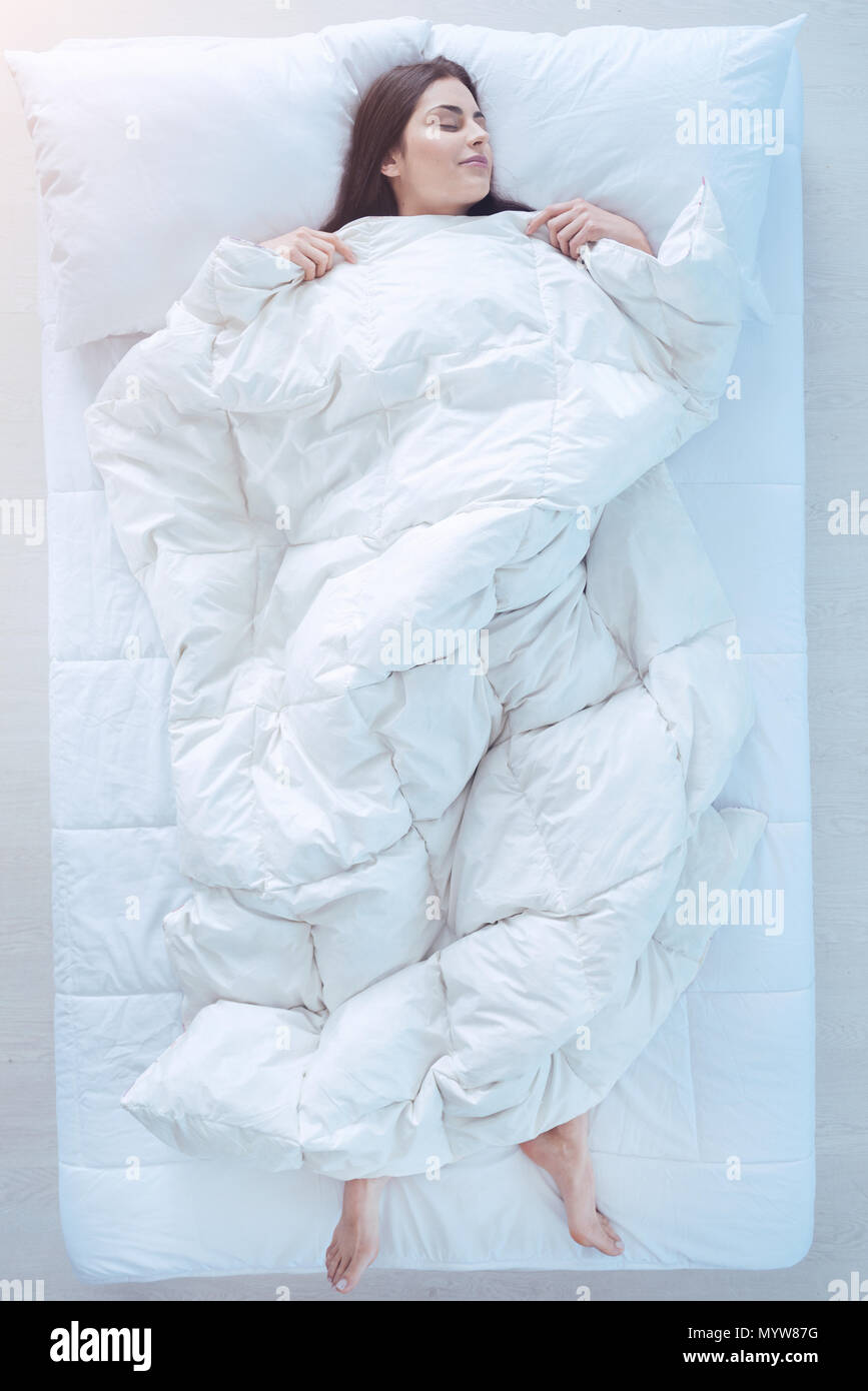 Young lady sleeping in bed with duvet over - Stock Image