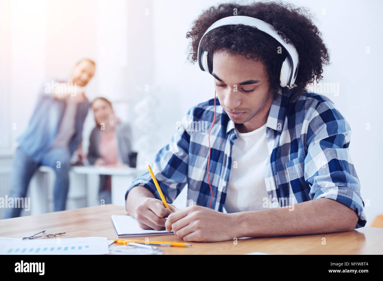 Concentrated foreign male person having headphones - Stock Image