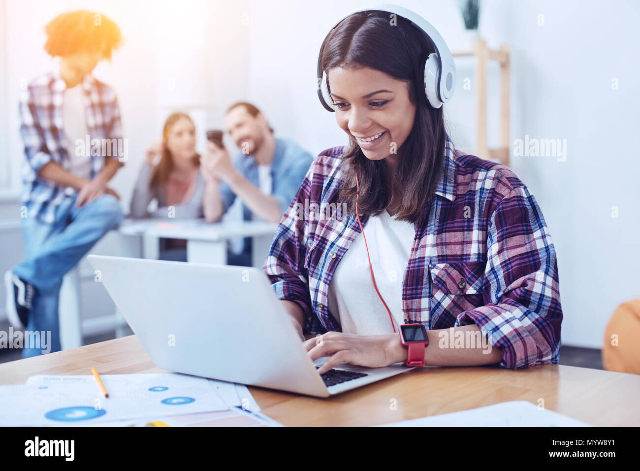 Delighted female wearing headphones while working - Stock Image