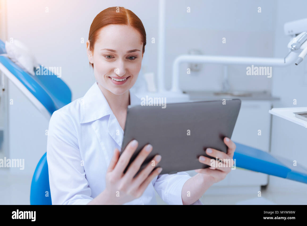 Positive delighted stomatologist sitting in her cabinet - Stock Image