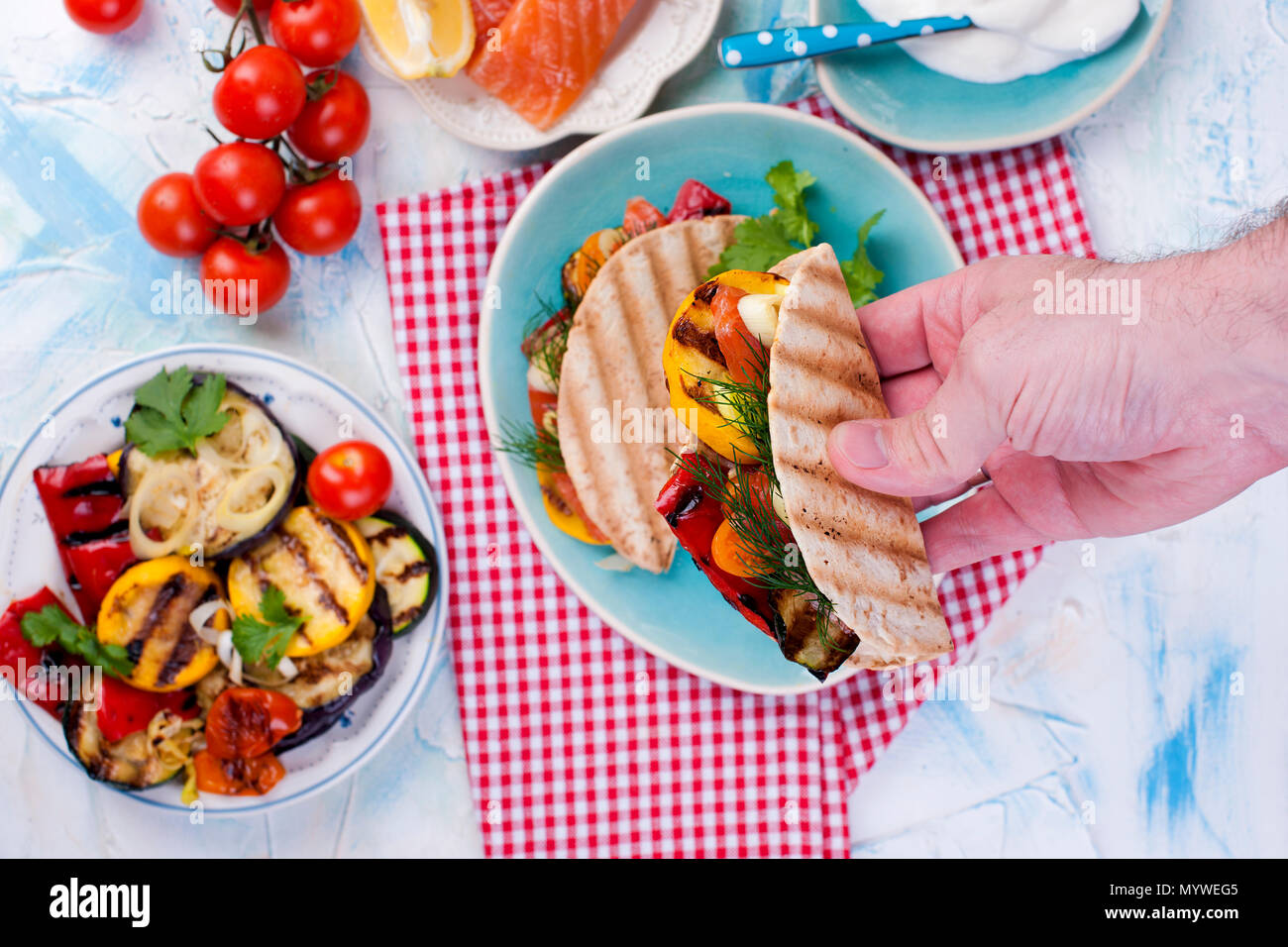 tortilla with vegetables and salmon in male hands. Fitness food. Healthy lunch. . - Stock Image