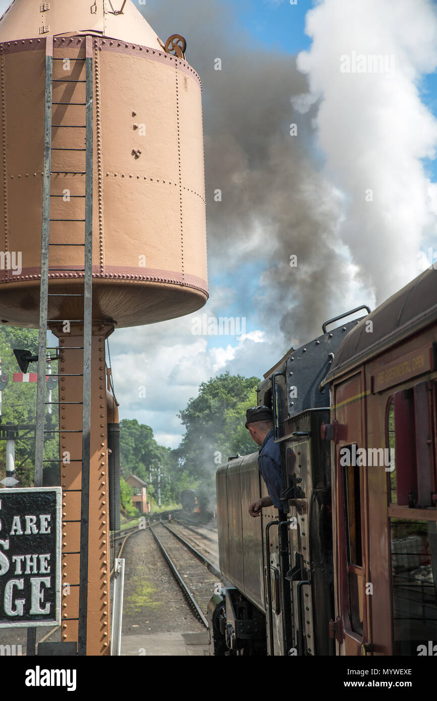 Portrait side view of steam locomotive awaiting departure, SVR Bewdley station. At water tower, steam & smoke plumes billow from engine. Driver waits. - Stock Image