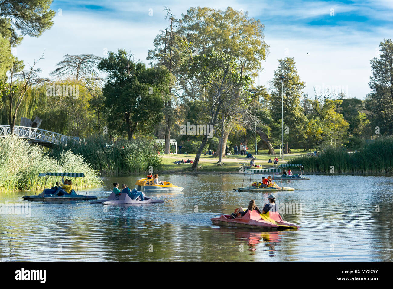 A Lake in a urban park. There are people using pedal boats on their weekend. It is a sunny day. - Stock Image