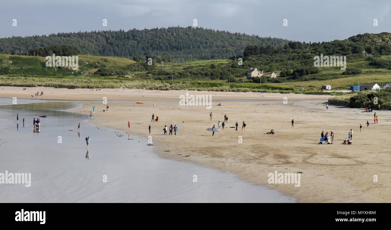 People on Marble Hill beach in County Donegal Ireland as summer surf schools take place in the Atlantic surf. - Stock Image