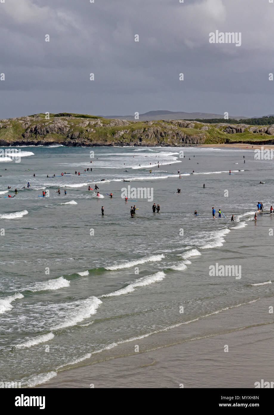 Groups of people surfing in County Donegal Ireland as summer surf schools take place in the Atlantic surf. - Stock Image