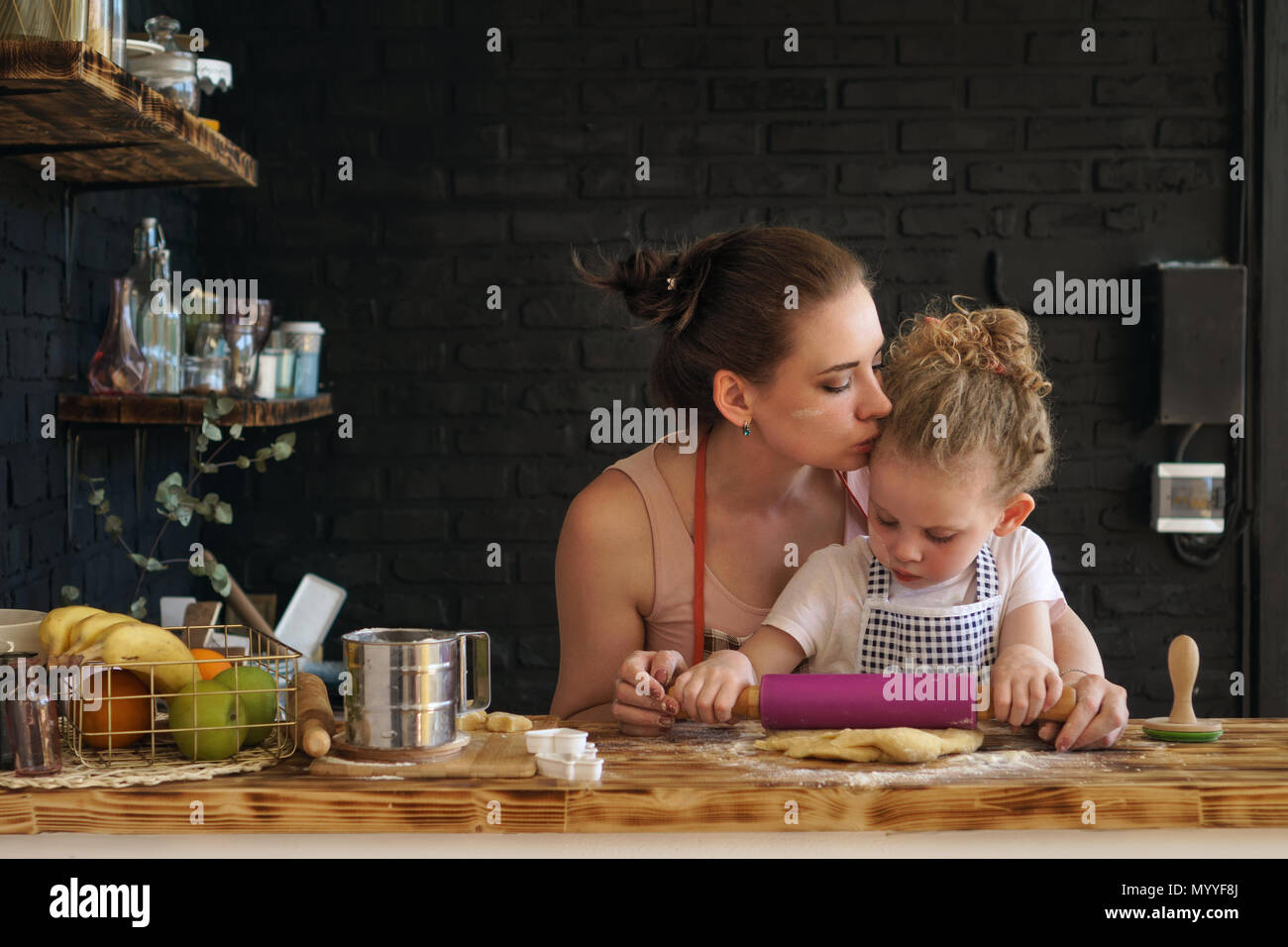 Young mother and daughter prepare cookies in kitchen. They are in aprons. Little girl rolls dough with rolling pin. Mother kisses child, encouraging - Stock Image