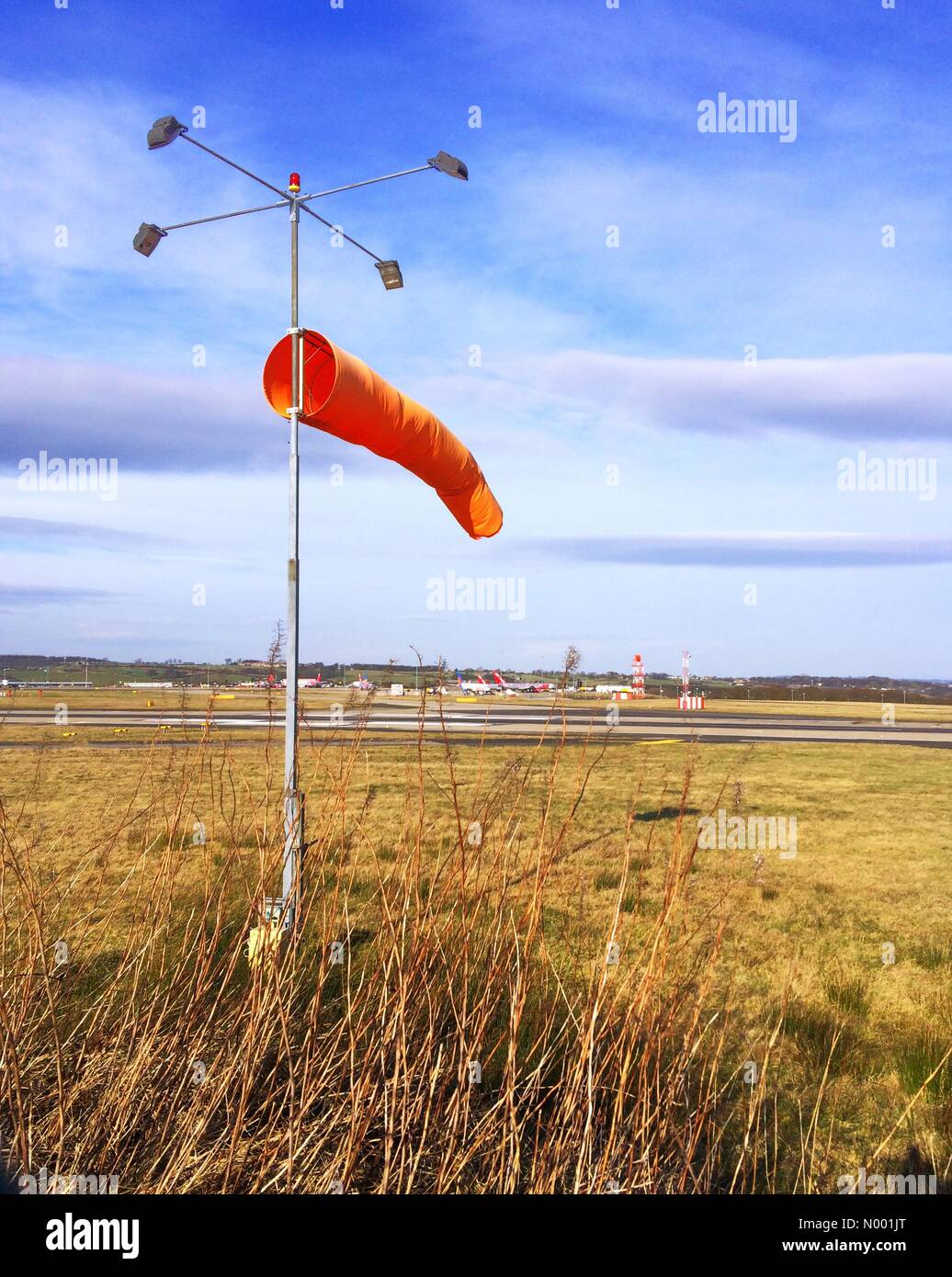 Sunny weather but strong winds producing tricky crosswind at Leeds Bradford International Airport Yeadon Leeds - Stock Image