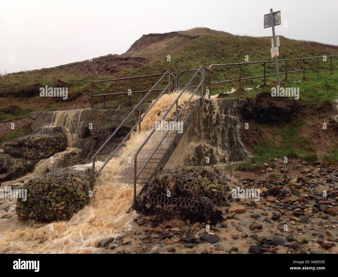 Flood water gushing down steps onto Cayton Beach Stock Photo