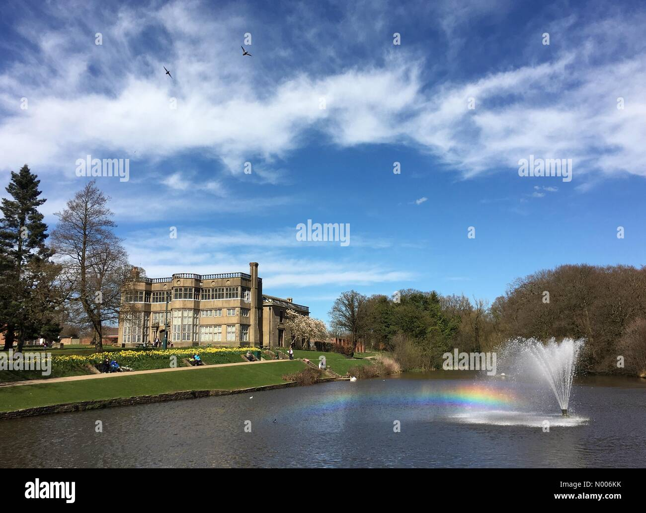 UK Weather sunny Sunday afternoon at Astley Park in Chorley, Lancashire. Rainbow cast by fountain in front of Astley - Stock Image