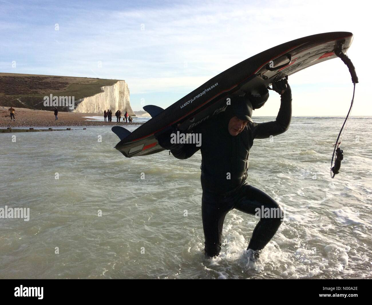 Cuckmere, East Sussex. 26th December 2016. Jet surfer leaving the sea on a sunny Boxing Day at the Sussex Coast. - Stock Image