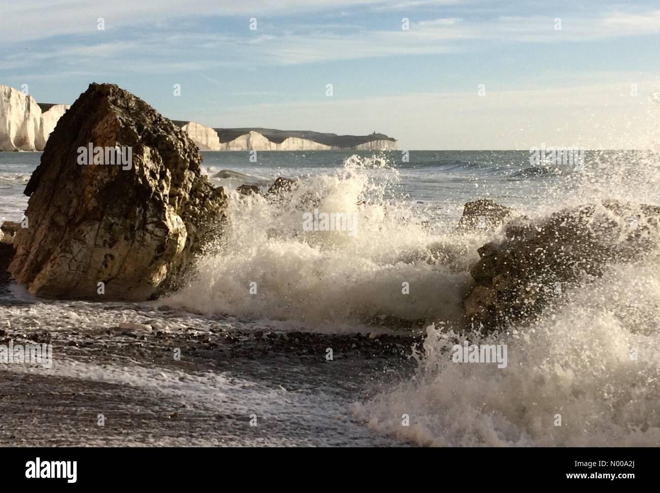 East Sussex. 26th December 2016. Waves hitting rocks on a sunny Boxing Day at the coast near the iconic Seven Sisters - Stock Image