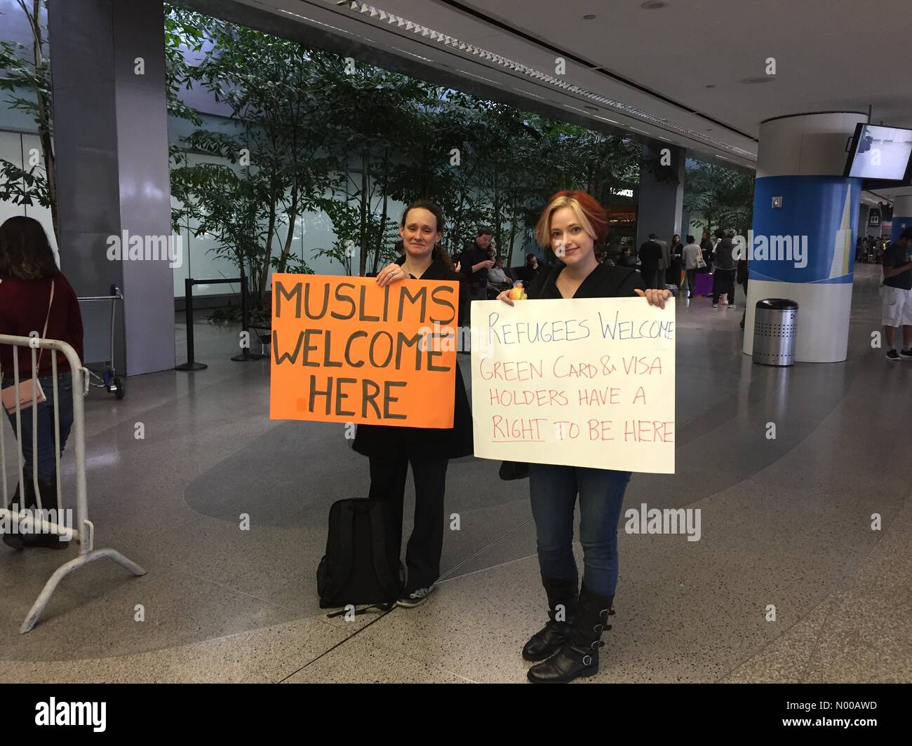 Millbrae, California, USA. 30th Jan, 2017. Protesters hold signs at the international arrival area of San Francisco - Stock Image