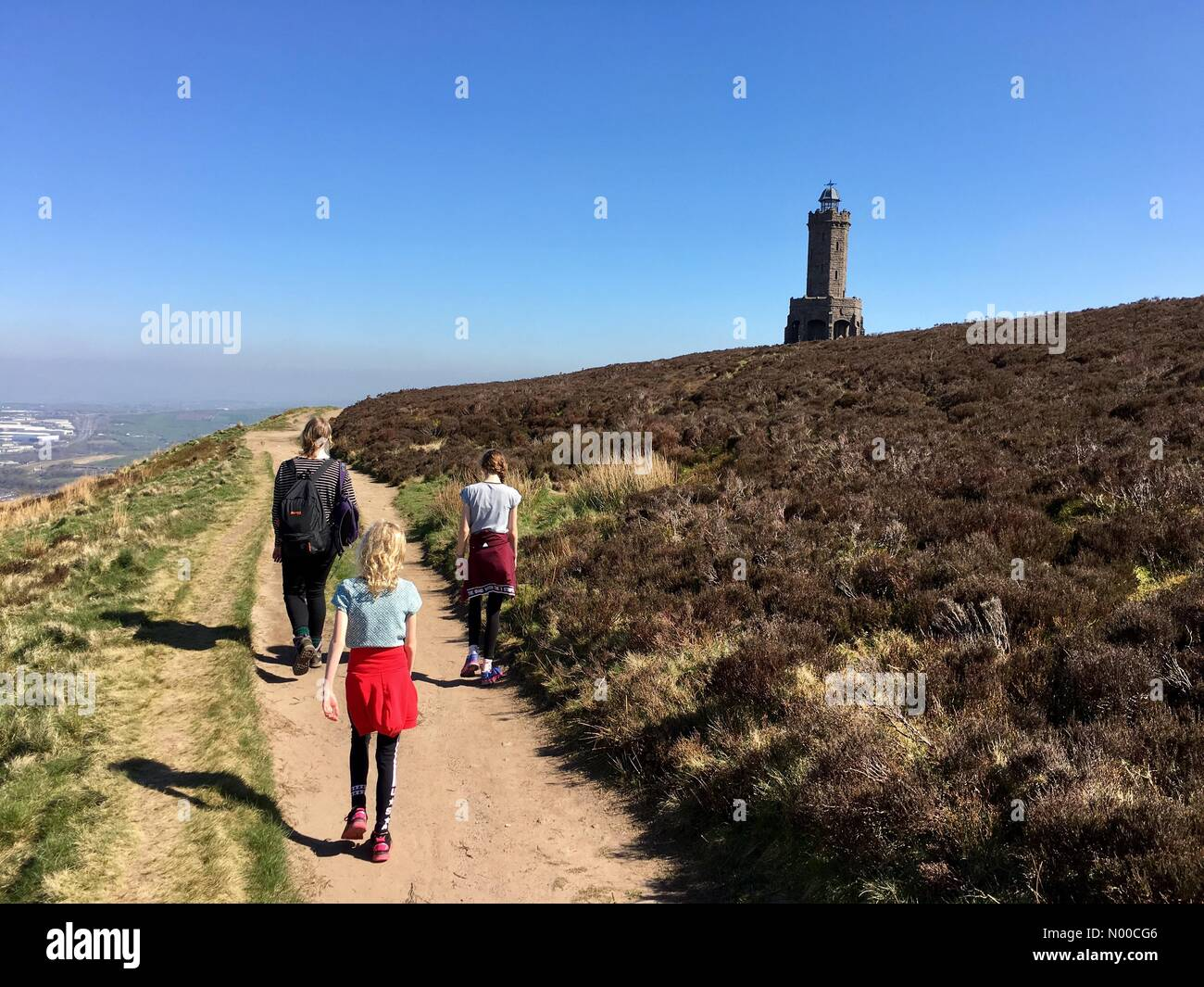 Uk Weather Day In Blackburn Lancashire Family Walking In Sun Towards Darwen Tower On The Moors Above Blackburn