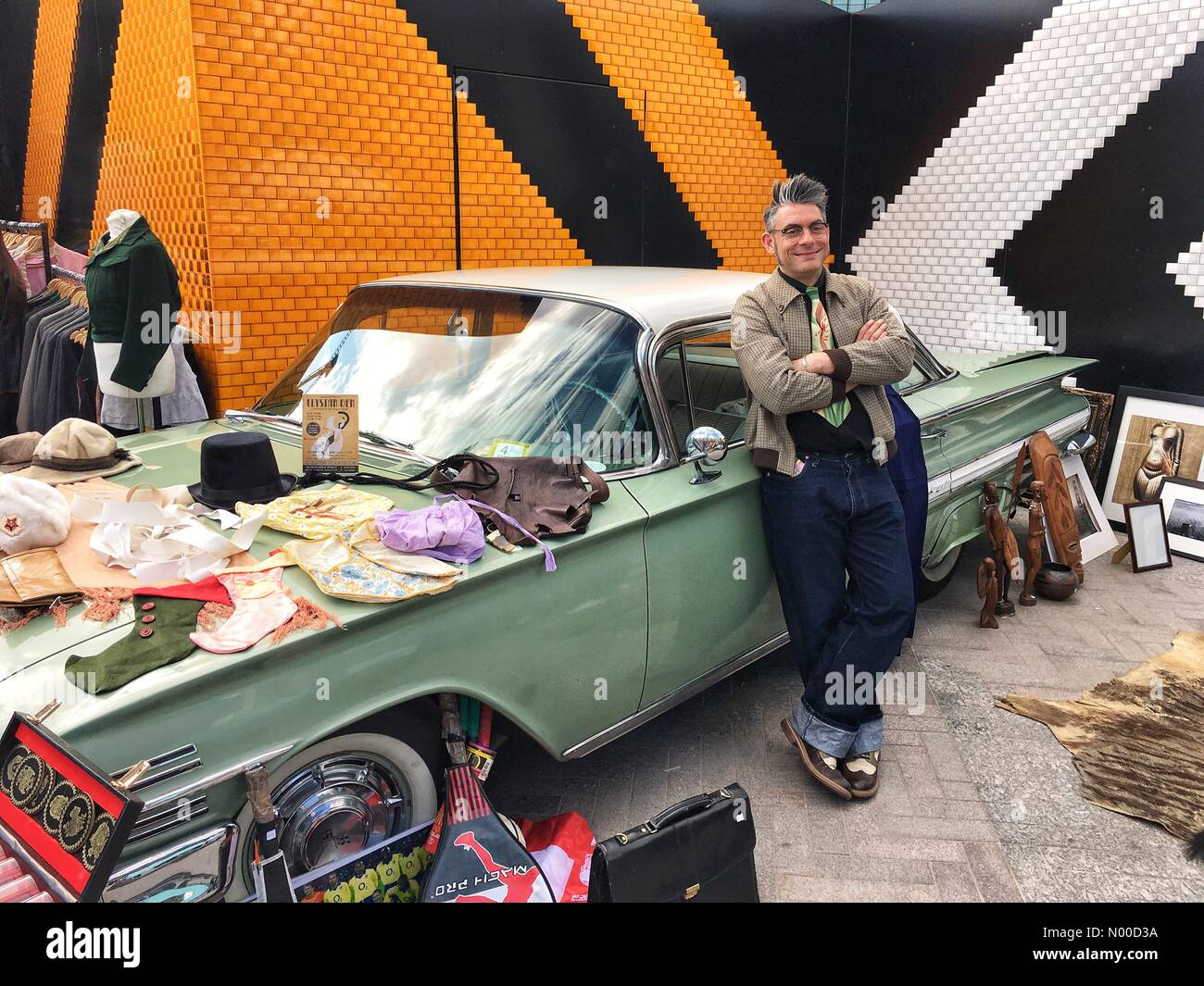 Stable St, London, UK. 23rd Apr, 2017. A trader lined up next to a vintage car at the Classic Car Boot Sale in Granary Stock Photo