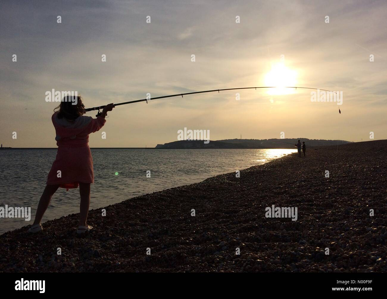 Seaford, East Sussex. 20th June 2017. A girl in a pink dressing gown fishing on the beach at the end of another - Stock Image