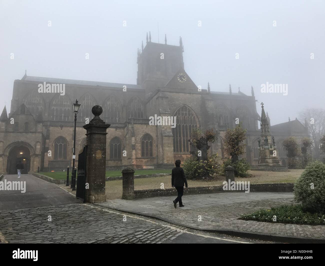UK Weather. Sherborne, UK. 2nd November, 2017. Fog descends  on Sherborne Abbey in Dorset with a Met Office yellow - Stock Image