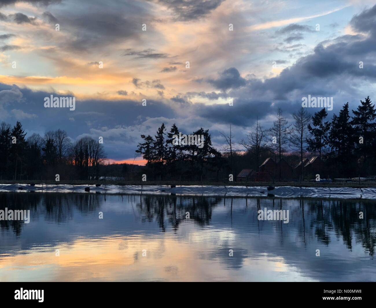 Godalming, UK. 28th Mar, 2018. UK Weather: Stormy sunset over Godalming. Tuesley Farm, Godalming. 28th March 2018. A stormy end to the day for the Home Counties. Sunset over Tuesley Farm in Godalming, Surrey. Credit: jamesjagger/StockimoNews/Alamy Live News - Stock Image