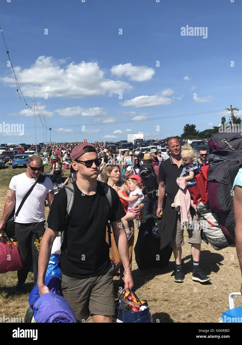 East Cowes, Newport, UK. 21st June, 2018. Seaclose Park, Newport, Isle of Wight. 21st Jun 2018. Hundreds of festival-goers enter the Isle of Wight festival site after a long wait in the heat. Credit: amylaura/StockimoNews Credit: amylaura/StockimoNews/Alamy Live News - Stock Image