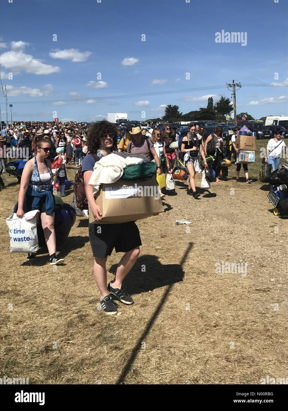 East Cowes, Newport, UK. 21st June, 2018. Seaport Close, Newport, Isle of Wight. 21st Jun, 2018. Festival-goers carry boxes and luggage after a long wait to enter the Festival site. Credit: amylaura/StockimoNews Credit: amylaura/StockimoNews/Alamy Live News - Stock Image
