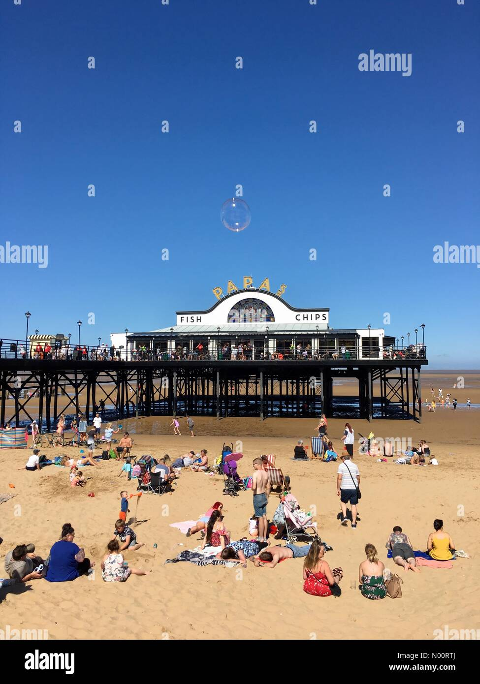Cleethorpes, UK, 30 June 2018.  Tourists enjoying the beautiful weather at Cleethorpes beach by the pier during the armed forces event, a lone bubble floats by. Cleethorpes N.E Lincolnshire, England UK Credit: narrative22/StockimoNews/Alamy Live News - Stock Image