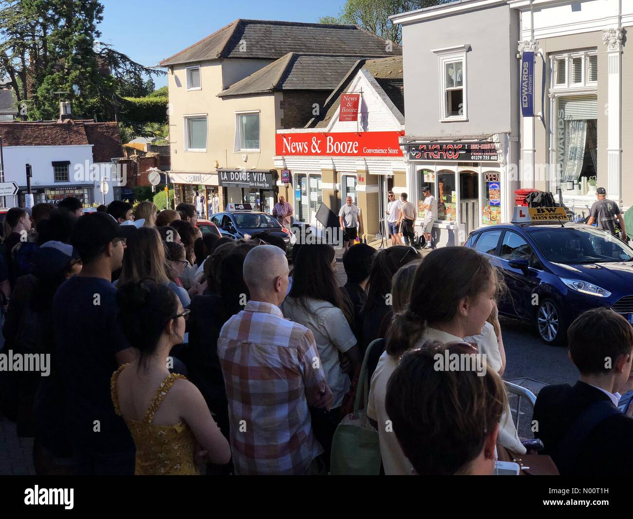 Crowds collect outside convenience store in Bishops Stortford, Hertfordshire where scenes for Spider-Man Far From Home have been filmed Stock Photo