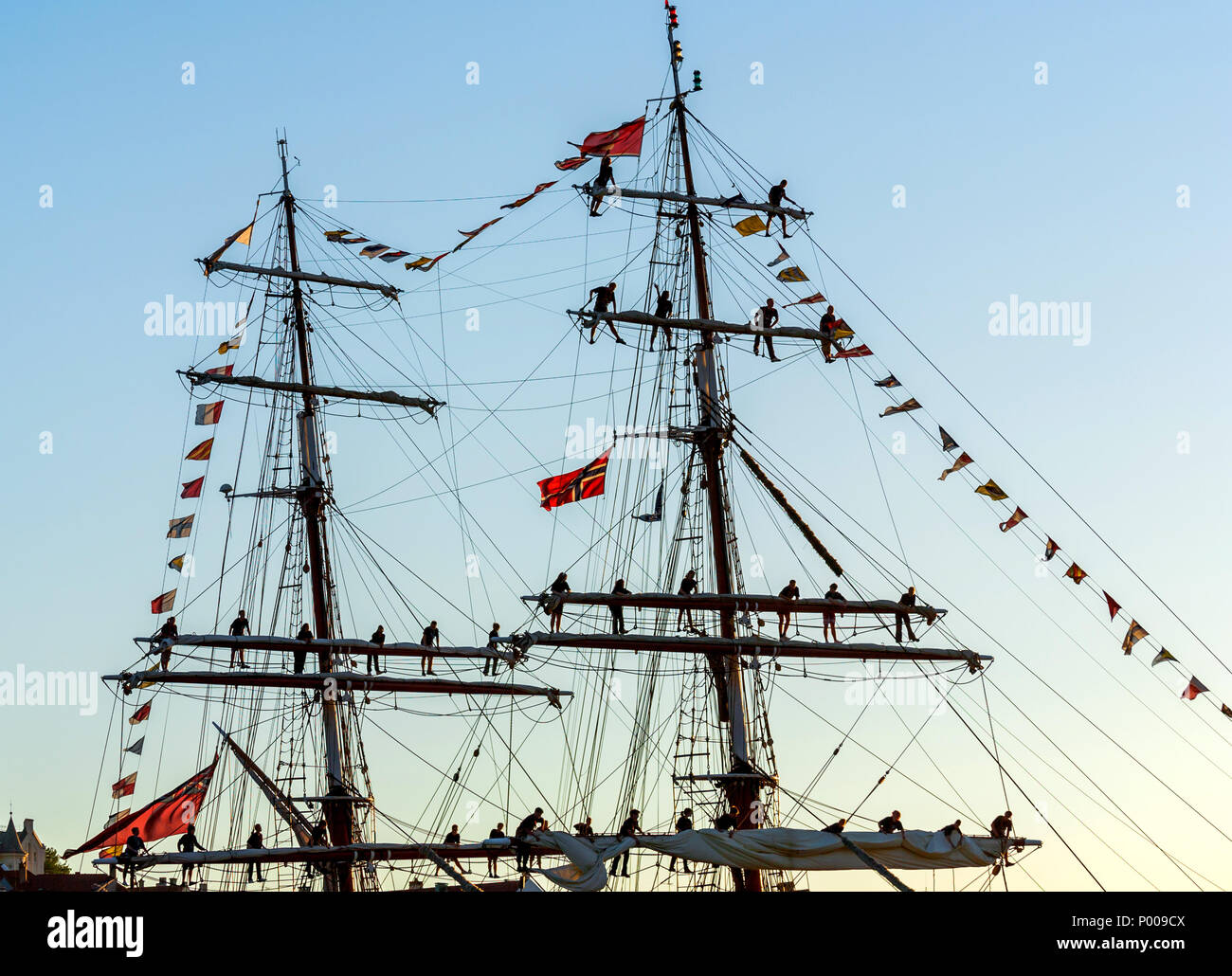 """Tall Ships Race 2008. Bergen, Norway - August 2008 The UK flagged """"Stavros S Niarchos"""" (brig) arriving port in the evening, with crew in the masts. Stock Photo"""
