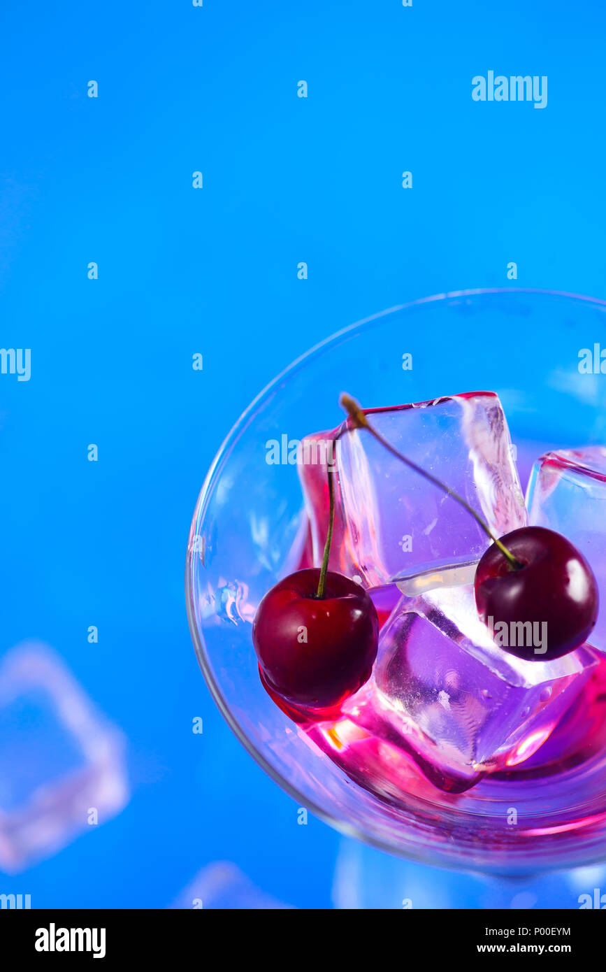 Cherry cocktail close-up. Martini glass with ice cubes and cherries on a bright blue background with copy space. Hot summer day refreshment concept - Stock Image