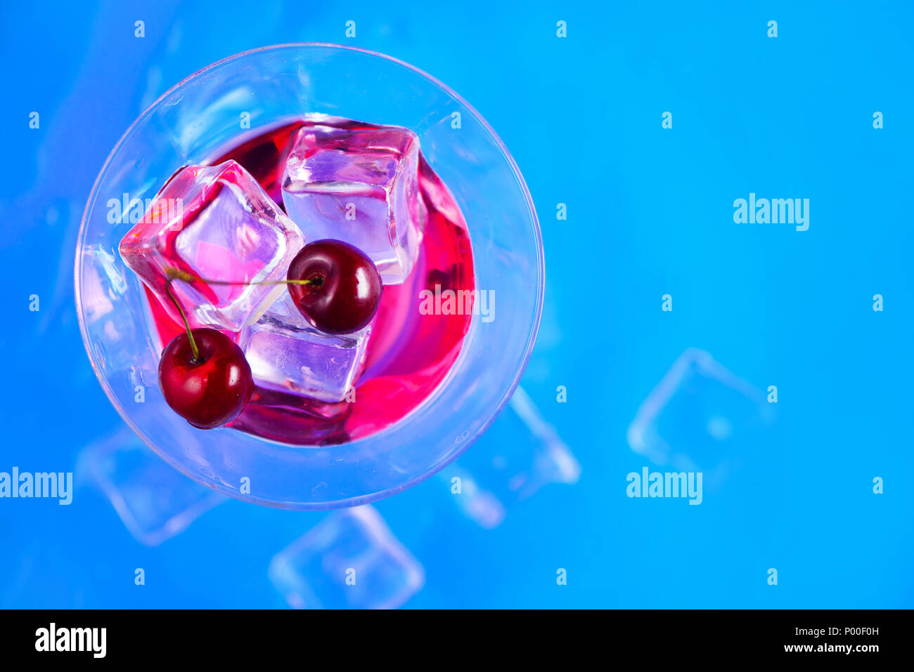 Cherry liquor cocktail glass from above on a blue background. Refreshing cold drink flat lay with copy space - Stock Image