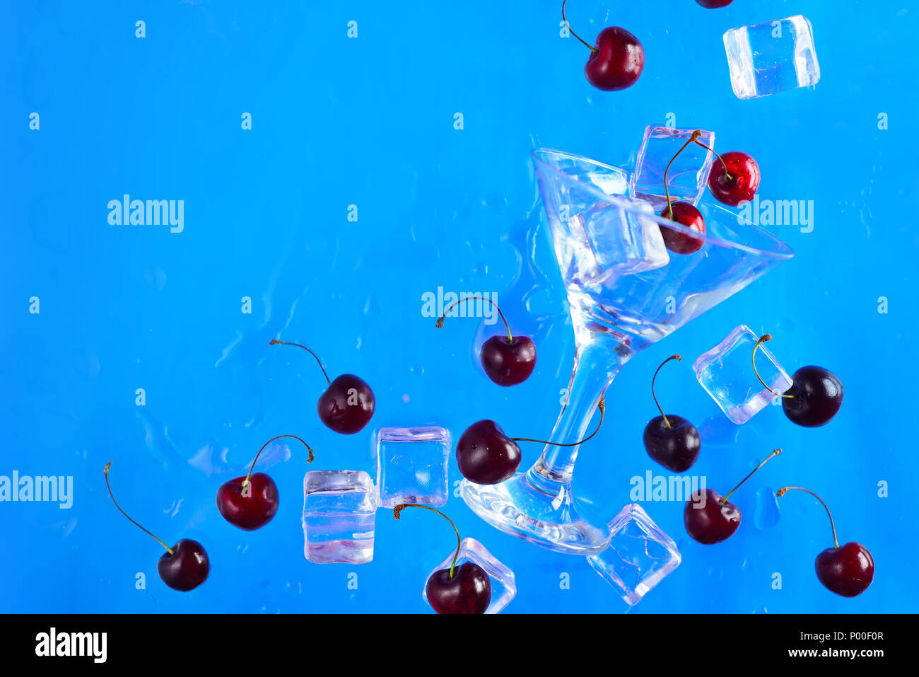 Martini glass with ice cubes and cherries on a bright blue background with copy space. Refreshing cold drink concept flat lay. - Stock Image
