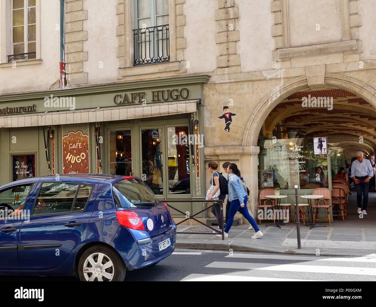 Pedestrians outside Cafe Hugo and the arcaded buildings of Place des Vosges, Paris, France - Stock Image