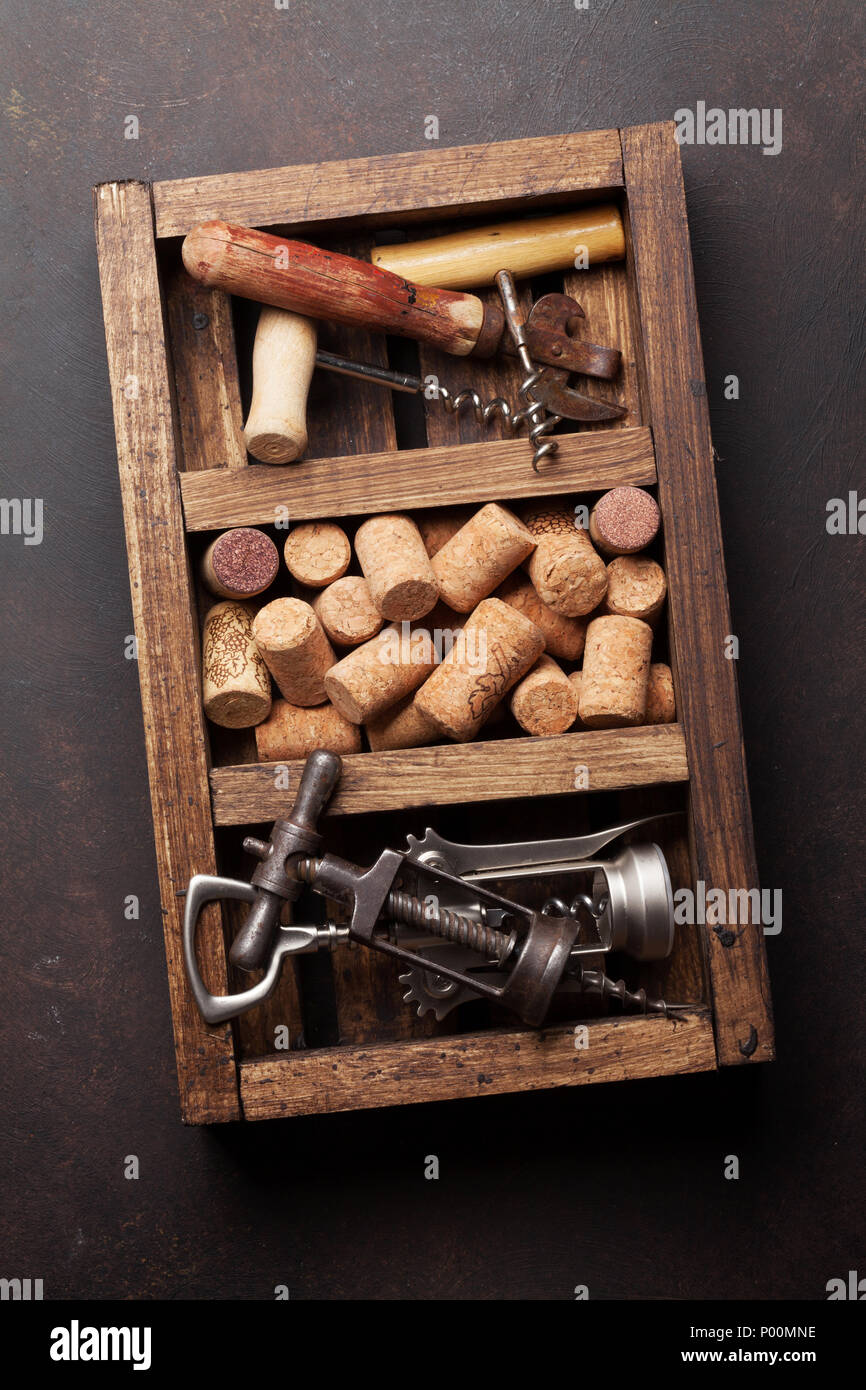 Wine corkscrews and corks in wooden box. Top view - Stock Image