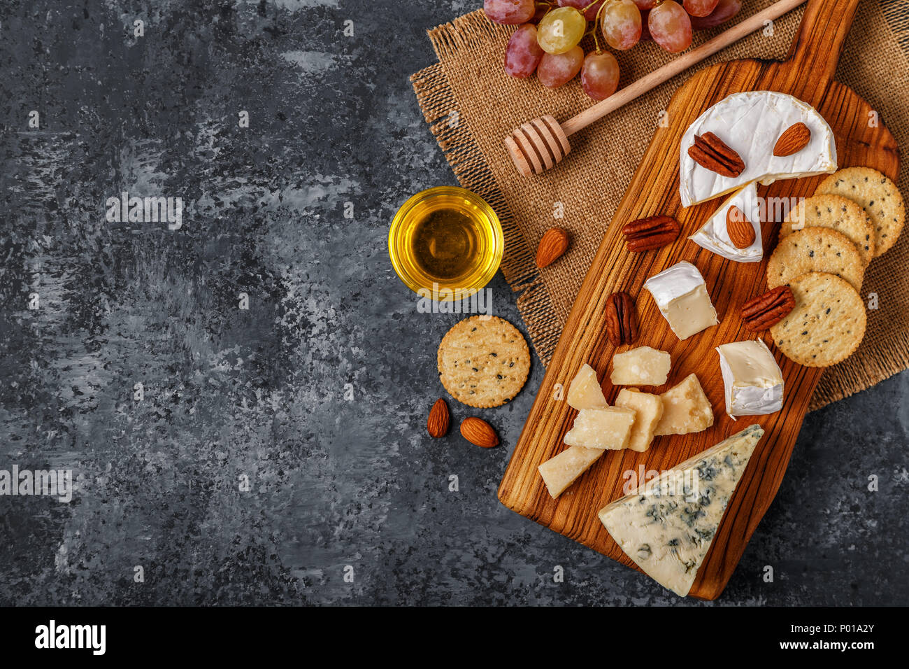 Assortment of cheese with honey, nuts and grape on a cutting board, top view. - Stock Image