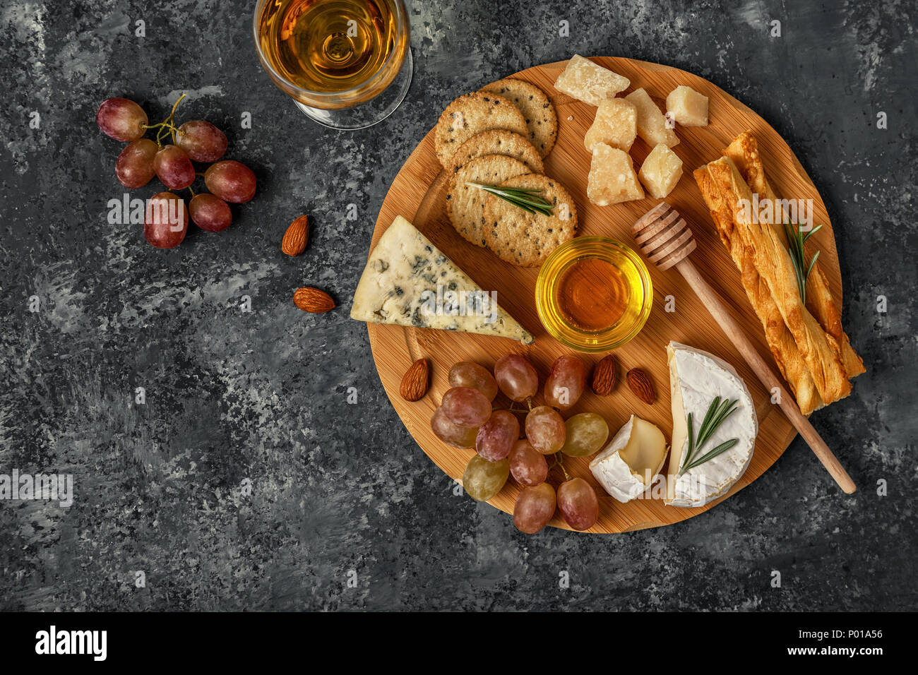 Assortment of cheese with wine, honey, nuts and grape on a cutting board, top view. - Stock Image