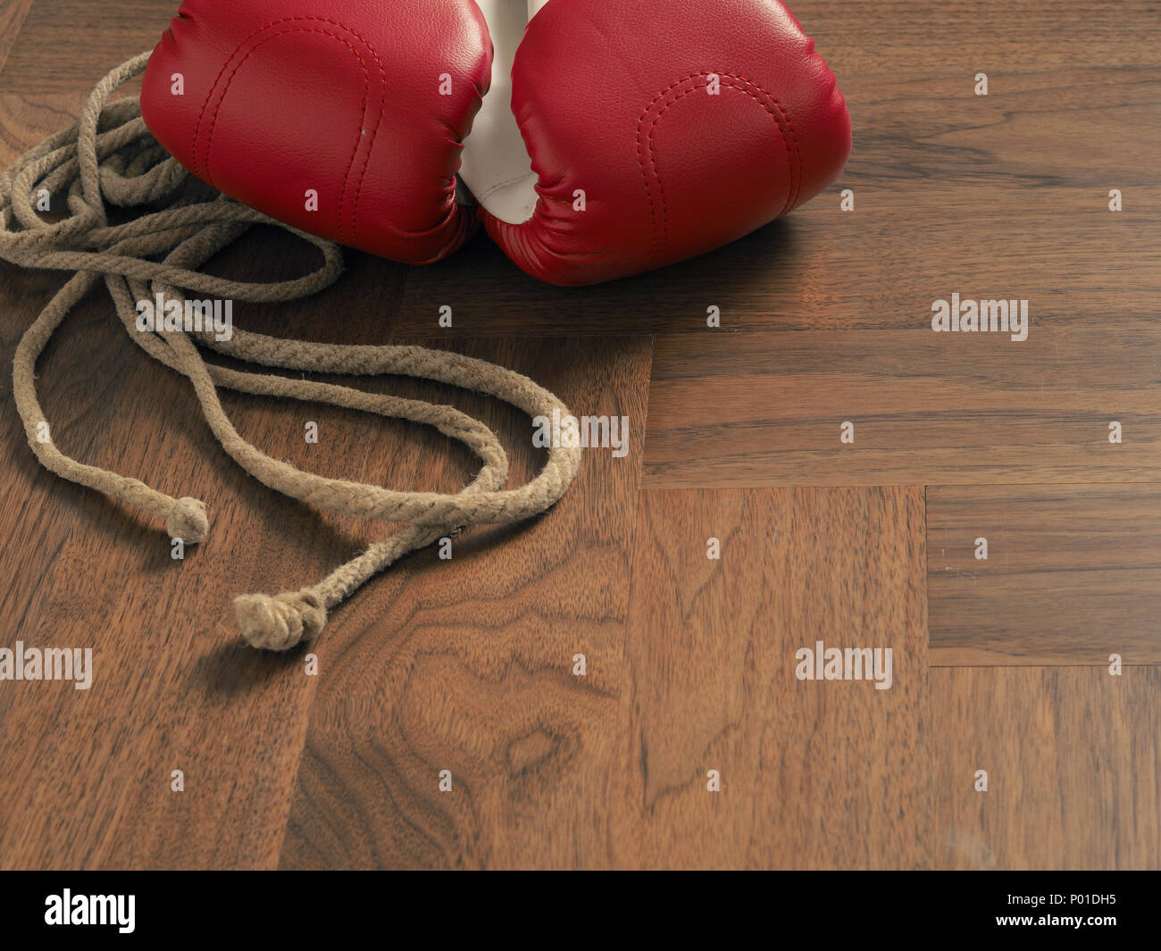 Red boxing gloves with a skipping rope on a wooden background - Stock Image