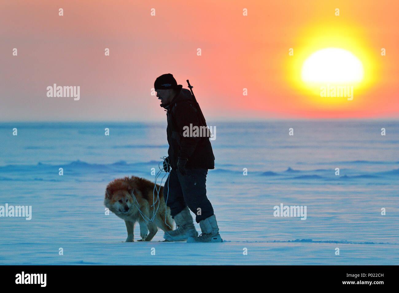 Bewaffneter Inuit mit Husky, Sonnenuntergang im Nunavut Territorium, Kanada | Armed Inuit with Husky, sunset at Nunavut teritorry, Canada - Stock Image