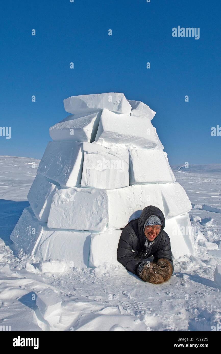 Inuit schaut aus einem Iglu, Nunavut Territorium, Kanada   Inuit looks out of a igloo, Nunavut teritorry, Canada - Stock Image