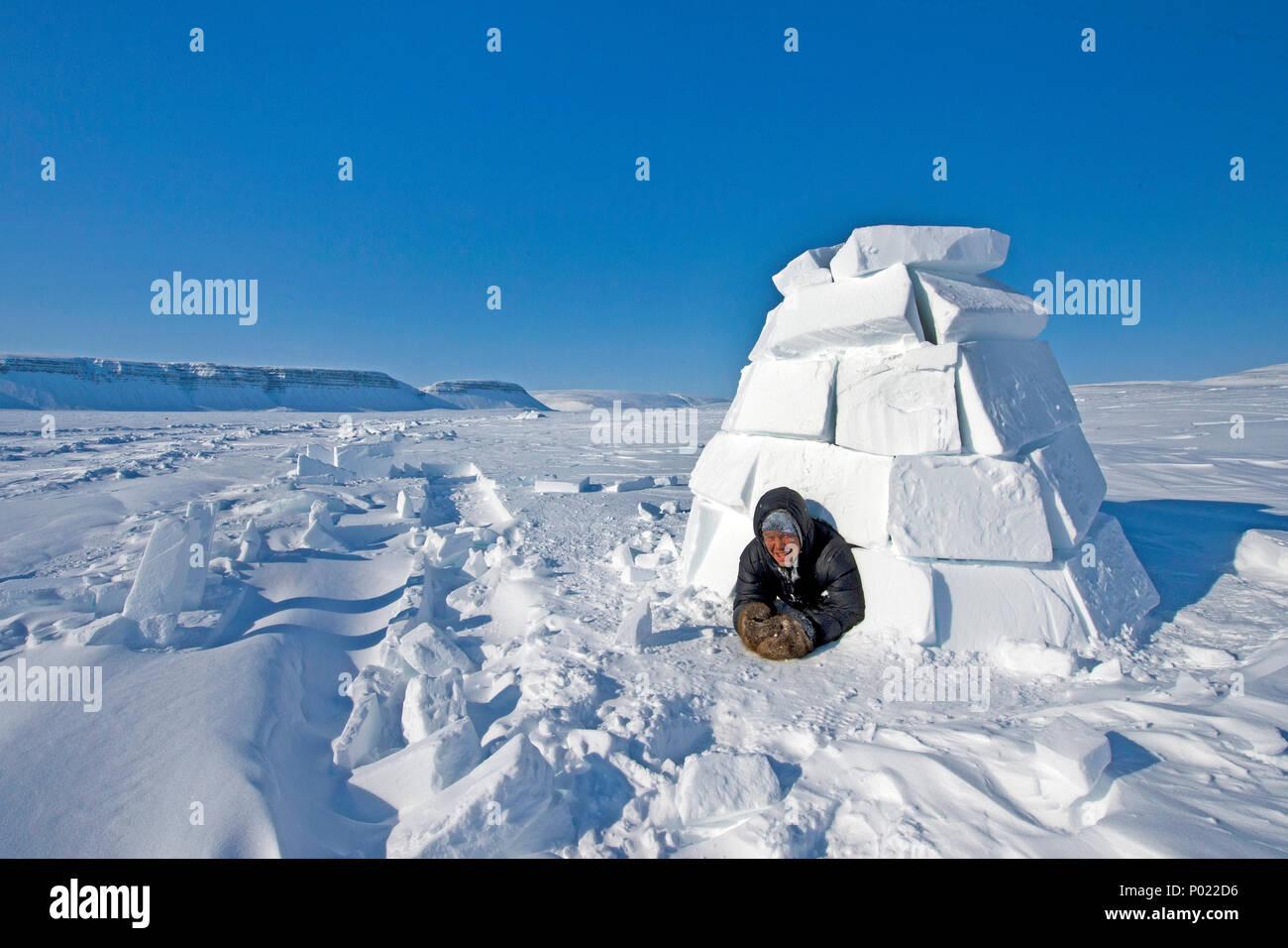 Inuit schaut aus einem Iglu, Nunavut Territorium, Kanada | Inuit looks out of a igloo, Nunavut teritorry, Canada - Stock Image