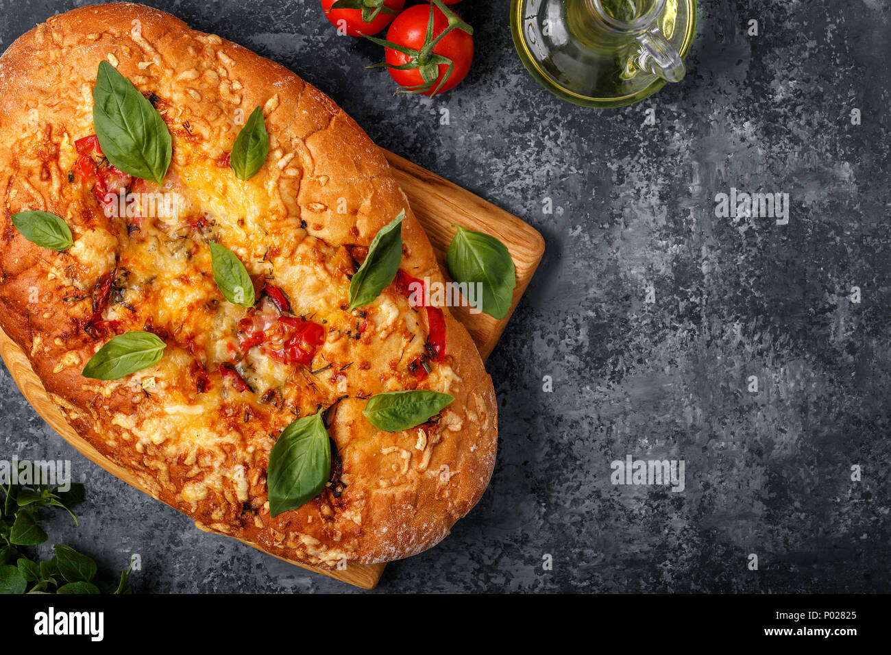 Focaccia with tomatoes, herbs and cheese, garnished with basil leaves. Stock Photo