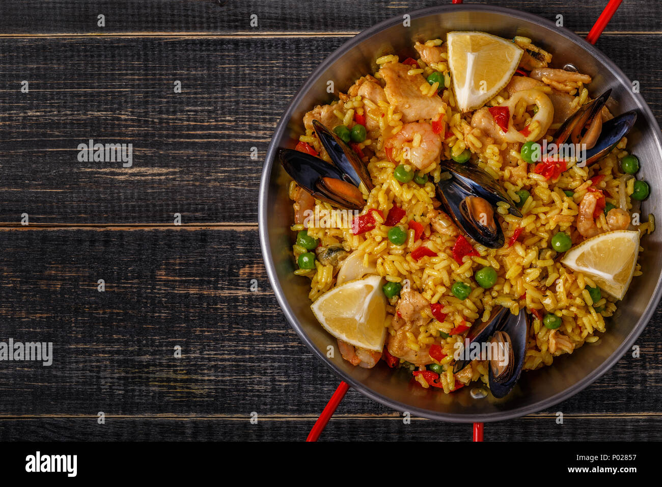 Paella with chicken,  seafood, vegetables and saffron served in the traditional pan, top view. - Stock Image