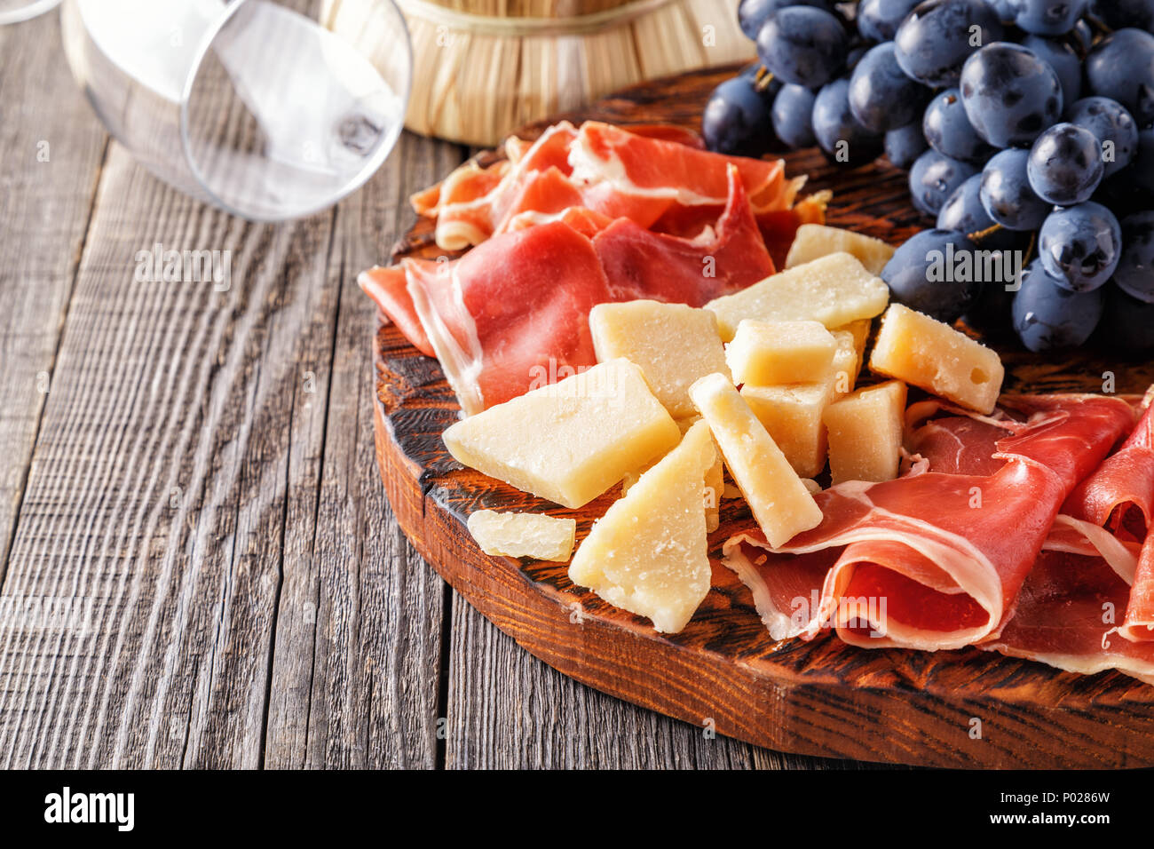 Prosciutto, wine, grape, parmesan on wooden table, selective focus. - Stock Image