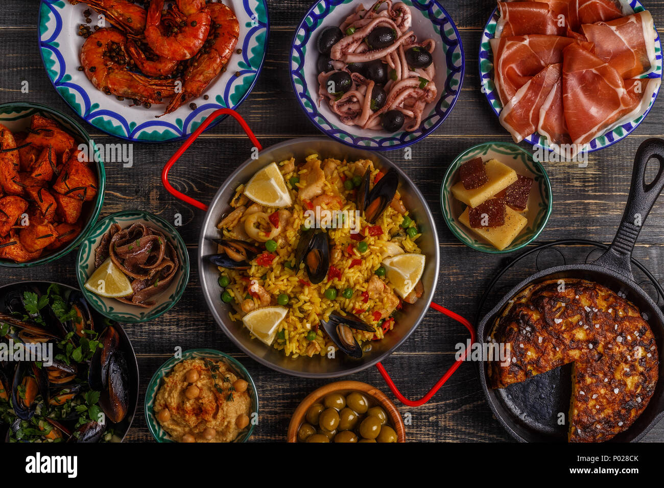 Typical spanish tapas concept. Concept include slices jamon, bowls with olives,  anchovies, spicy potatoes, mashed chickpeas, shrimp, calamari, manche Stock Photo