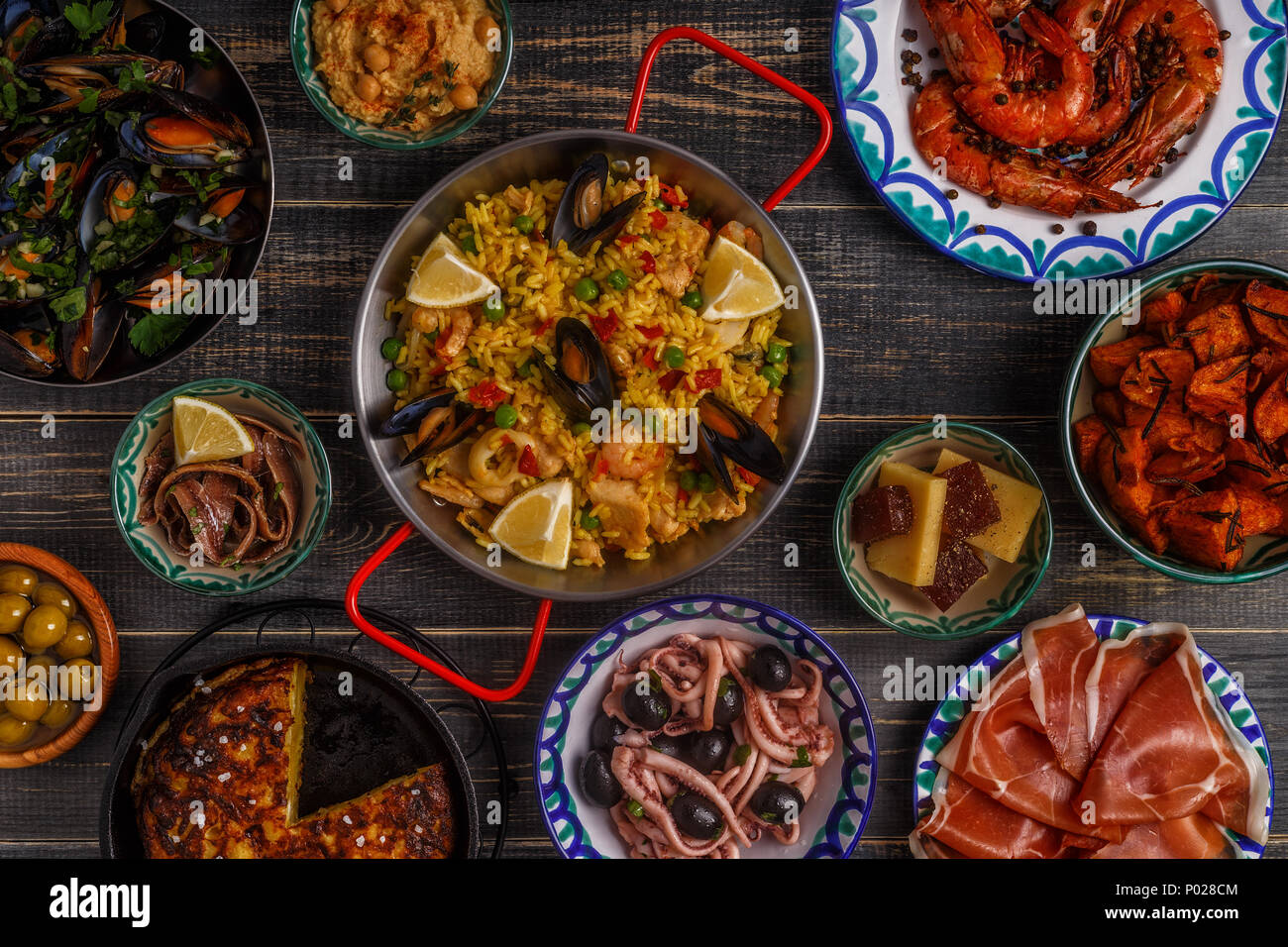 Typical spanish tapas concept. Concept include slices jamon, bowls with olives,  anchovies, spicy potatoes, mashed chickpeas, shrimp, calamari, manche - Stock Image