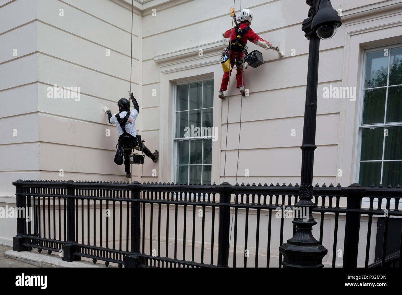 Abseiling painters put a fresh coat of colour on the exterior of the Laneborough Hotel at Hyde Park Corner, on 8th June 2018, in London, England. - Stock Image