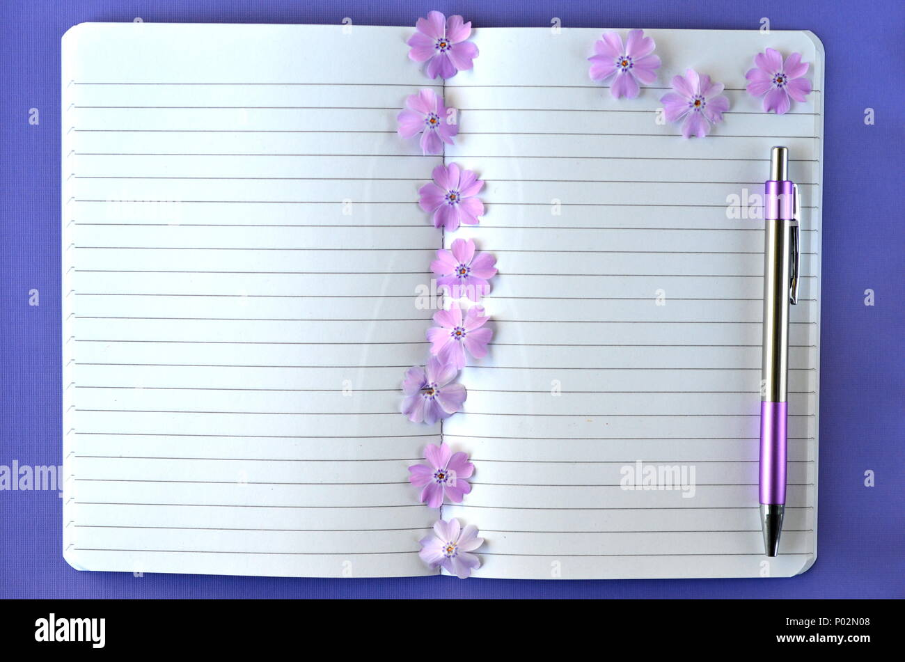 Ultra violet flatlay of feminine stationery, notebook, pen, lavender phlox flowers with copy space. Brainstorming ideas, note taking or diary writing - Stock Image