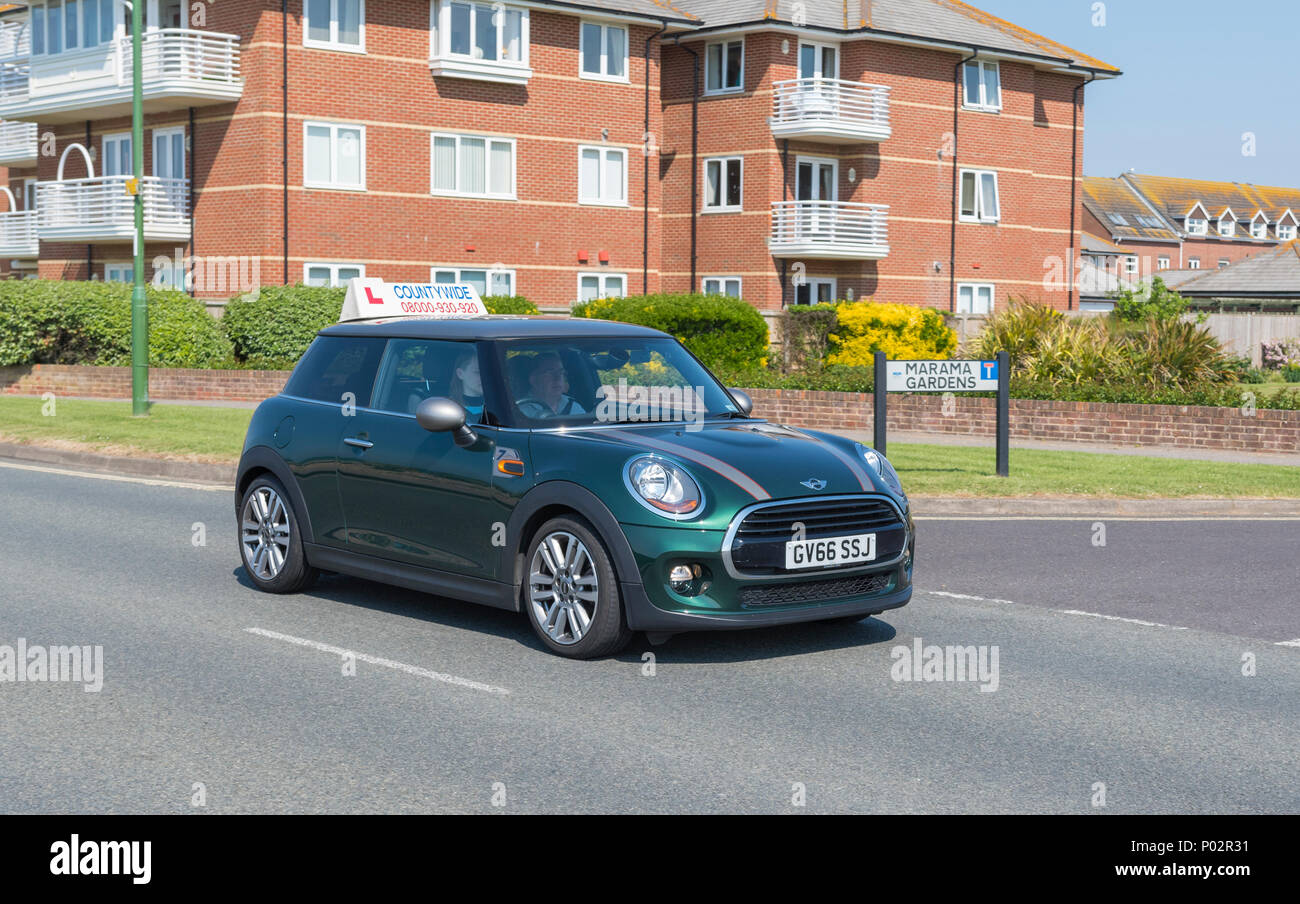 Someone driving a Mini car with L learner plates, presumably taking a driving lesson to learn to drive on a British road in England, UK. - Stock Image
