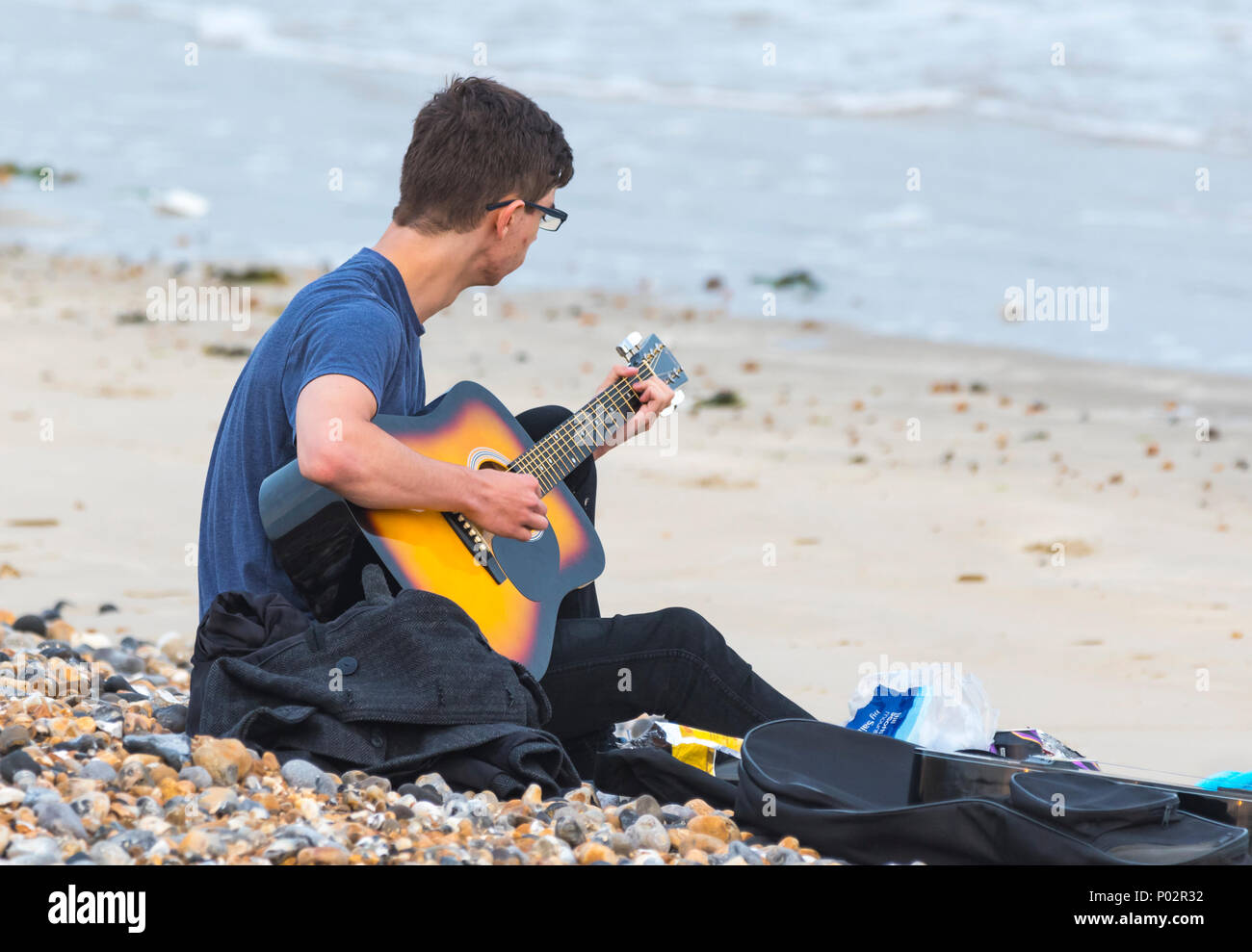 Young man sitting on a sandy beach playing a guitar, in the UK. - Stock Image